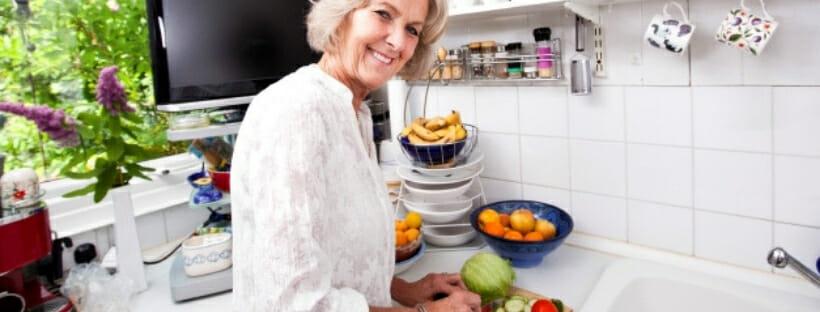 Woman in the kitchen peeling a fruit