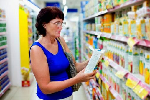 old woman in grocery looking at food label